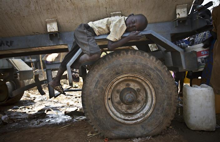 A young displaced boy rests on the wheel arch of a water truck while others fill containers from it, at a United Nations compound which has become home to thousands of people displaced by the recent fighting, in the Jebel area on the outskirts of Juba, South Sudan Tuesday, Dec. 31, 2013. Anti-government rebels took control of nearly all of the strategic city of Bor on Tuesday even as officials announced that representatives from the government and the rebels had agreed to hold talks for the first time. (AP Photo/Ben Curtis)