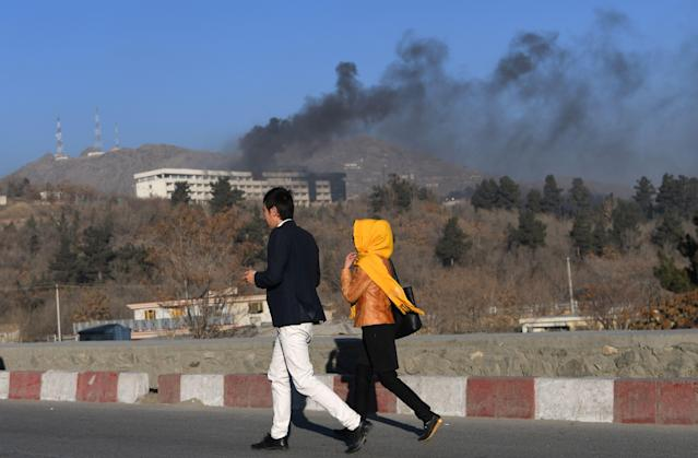 <p>Afghans walk near the Intercontinental Hotel as smoke billows during a fight between gunmen and Afghan security forces in Kabul on January 21, 2018. (Photo: Wakil Kohsar/AFP/Getty Images) </p>