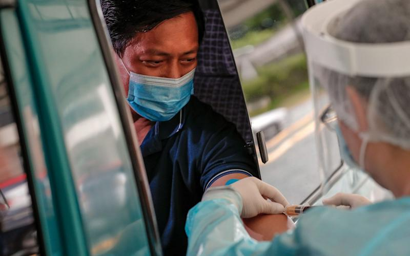 A health worker performs drive-thru antibody testing at a testing facility at the Medical City in Ortigas, east of Manila, Philippines - Shutterstock