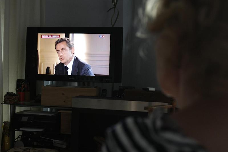 A woman watches an interview with former French President Nicolas Sarkozy, after he was charged with corruption and influence peddling, in Caen, northwestern France, on July 2, 2014 (AFP Photo/Charly Triballeau )