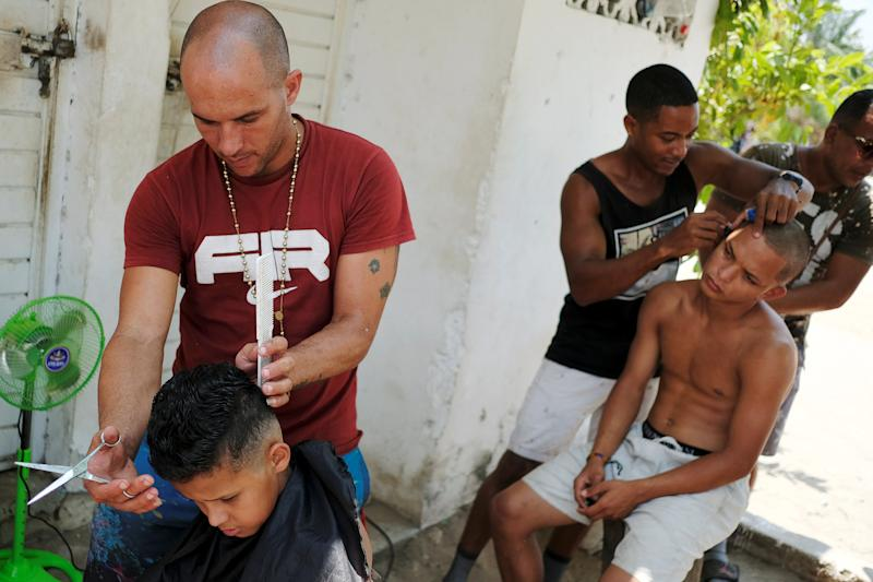 Cuban migrants cut the hair of young Honduran migrants at an improvised shelter while waiting for their humanitarian visas to cross the country on their way to the United States, in Mapastepec