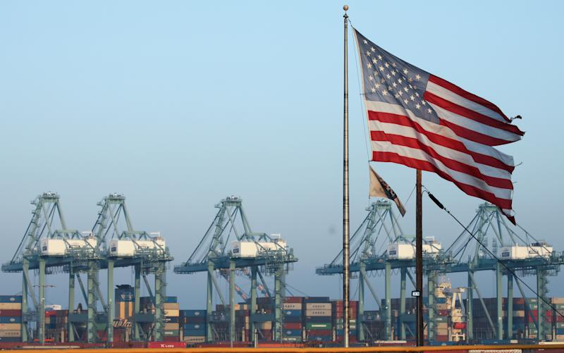 SAN PEDRO, CALIFORNIA - NOVEMBER 07: An American flag flies nearby with shipping containers stacked at the Port of Los Angeles in the background, which is the nation's busiest container port, on November 7, 2019 in San Pedro, California. Port officials said today October cargo volume was down 19 percent this year compared with October 2018 due to tariffs imposed in the U.S.-China trade war. The Port of Los Angeles along with neighboring Port of Long Beach are the United States' main gateways for trade with Asia. (Photo by Mario Tama/Getty Images)
