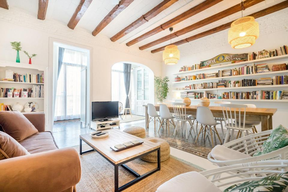"""This three-bedroom apartment in <a href=""""https://www.cntraveler.com/destinations/barcelona?mbid=synd_yahoo_rss"""" rel=""""nofollow noopener"""" target=""""_blank"""" data-ylk=""""slk:Barcelona's"""" class=""""link rapid-noclick-resp"""">Barcelona's</a> Eixample neighborhood mixes and matches the old with the new, pairing its clean, white design with antique rugs, exposed wooden beams, and a slew of texts of all ages. The open floor plan and bright natural light make every corner a great spot to read, too. $345, Airbnb (Starting Price). <a href=""""https://www.airbnb.com/rooms/plus/272282"""" rel=""""nofollow noopener"""" target=""""_blank"""" data-ylk=""""slk:Get it now!"""" class=""""link rapid-noclick-resp"""">Get it now!</a>"""