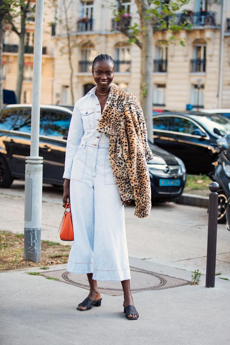 PARIS, FRANCE - SEPTEMBER 27: Model Agi Akur wears a white jumpsuit, orange Loewe bag, black sandals, and carries a leopard fur jacket after the Loewe show during Paris Fashion Week Spring/Summer 2020 on September 27, 2019 in Paris, France. (Photo by Melodie Jeng/Getty Images)