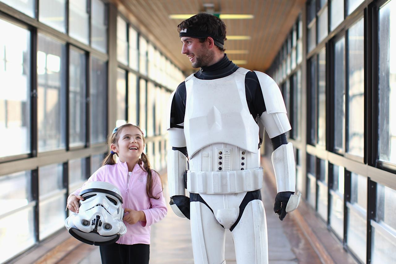SYDNEY, AUSTRALIA - APRIL 11:  Jacob French walks with patient Helena Kantarelis at the Sydney Children's Hostpital on April 4, 2012 in Sydney, Australia. French today completed the over 5,000 km trek from Perth to Sydney on foot, donning a full body stormtrooper costume he successfully raised over $100,000 for the Starlight Children's Foundation. Since July 2011, Jacob has walked 10 hours a day, Monday to Friday, lost over 12kg in weight, and gone through seven pairs of shoes. The Starlight Children's Foundation provides programs to help lift the spirits of sick children in hospitals accross Australia.  (Photo by Cameron Spencer/Getty Images)