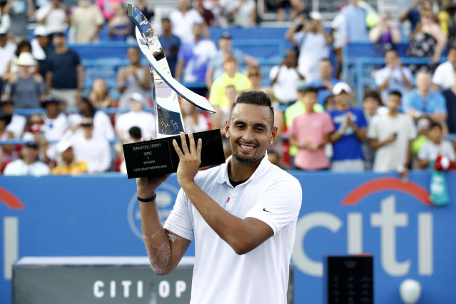 Nick Kyrgios, of Australia, poses for photos with a trophy after defeating Daniil Medvedev, of Russia, in a final match at the Citi Open tennis tournament, Sunday, Aug. 4, 2019, in Washington. (AP Photo/Patrick Semansky)