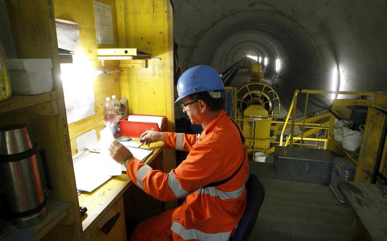 An engineer sits on the special train 'Helvetia' in the NEAT Gotthard Base tunnel near Erstfeld May 7, 2012. The train, which is 481 metres (1578 ft) long and weighs 787 tons, is constructed to produce concrete for the installation of the railway tracks in the tunnel. Crossing the Alps, the world's longest train tunnel should become operational at the end of 2016. The project consists of two parallel single track tunnels, each of a length of 57 km (35 miles)  REUTERS/Arnd Wiegmann   (SWITZERLAND - Tags: BUSINESS CONSTRUCTION EMPLOYMENT TRAVEL)