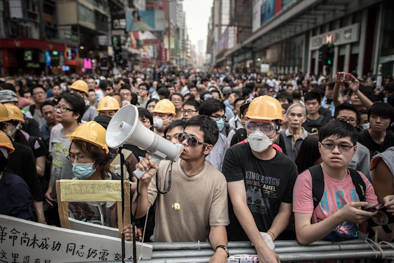 Pro-democracy demonstrators guard a barricade in the Mongkok district of Hong Kong on October 22, 2014 (AFP Photo/Philippe Lopez)