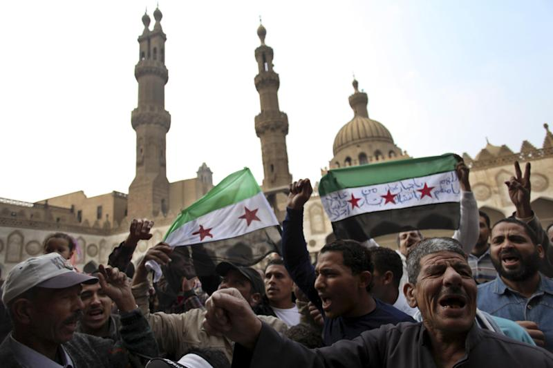 FILE - In this December 28, 2012, file photo, protesters chant slogans and wave the Syrian revolution flags during a rally after the Friday prayer at Al-Azhar mosque in Cairo, Egypt. The downfall of the Muslim Brotherhood in Egypt has shaken its Syrian counterpart and deepened distrust of the secretive movement by other Syrians who are suspicious of the Brotherhood's religious agenda. For Syria's banned Muslim Brotherhood, the uprising against President Bashar Assad that erupted amid Arab Spring revolts in 2011 provided a long-sought opportunity to stage a comeback after decades spent in exile. (AP Photo/Khalil Hamra, File)