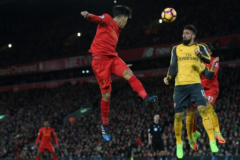 Liverpool's midfielder Roberto Firmino (C) heads the ball across goal during the English Premier League football match against Arsenal March 4, 2017