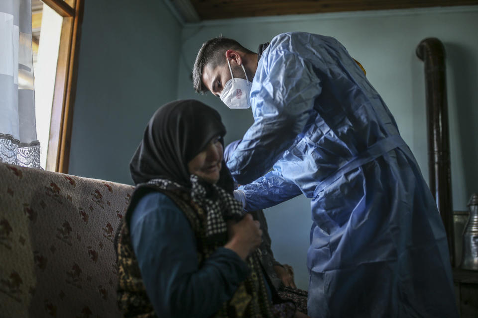 Zeynep Yigit, 70, left, is administered a dose of the CoronaVac vaccine made by China's Sinovac Biotech Ltd., by health worker Yusuf Duran at her house in the isolated village of Gumuslu in the district of Sivas, central Turkey, Friday, Feb. 26, 2021. Health care workers, older people and people with serious medical conditions were among the first to receive the jab. (AP Photo/Emrah Gurel)