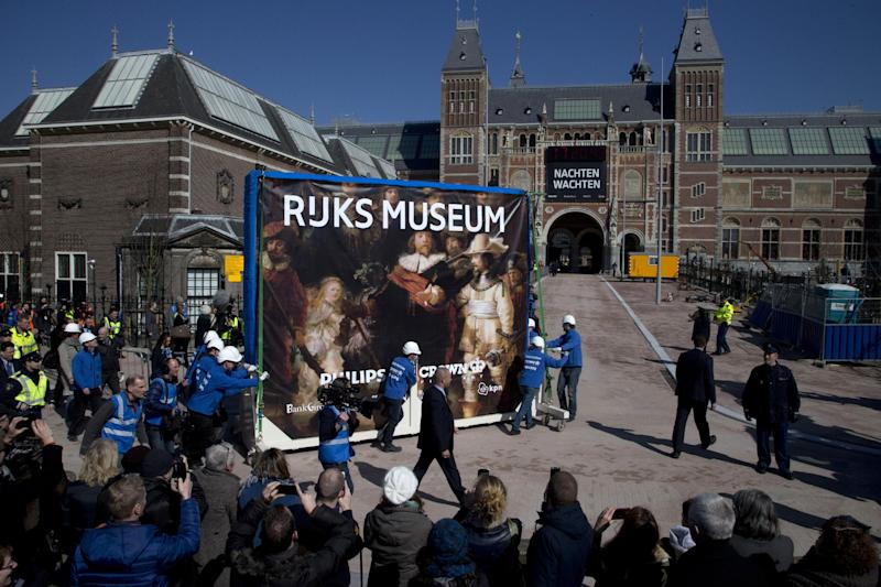 Workers push a crate containing Dutch master Rembrandt's famous Night Watch painting to its new location in the renovated Rijksmuseum, rear, in Amsterdam, Wednesday March 27, 2013. The museum will be opened officially on April 13, 2013, the crate was adorned with a reproduction of the painting. (AP Photo/Peter Dejong)