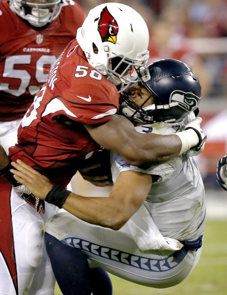 Seattle Seahawks quarterback Russell Wilson, right, takes a hit from Arizona Cardinals inside linebacker Daryl Washington during the first half of an NFL football game, Thursday, Oct. 17, 2013, in Glendale, Ariz. (AP Photo/Ross D. Franklin)