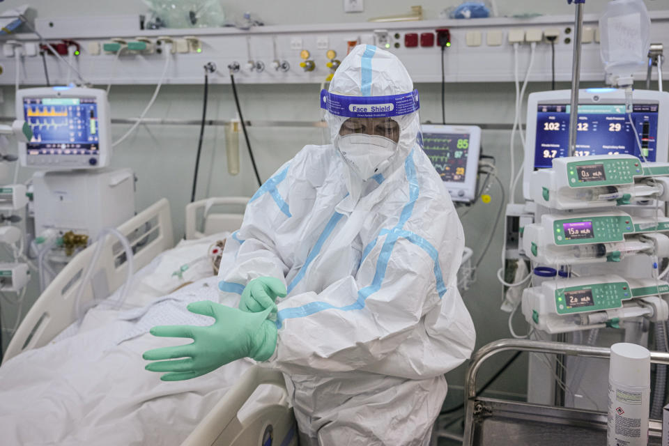 A member of the medical staff puts on an extra pair of gloves in the COVID-19 ICU unit of the Marius Nasta National Pneumology Institute in Bucharest, Romania, Thursday, Sept. 23, 2021. Daily new coronavirus infections in Romania, a country of 19 million, have grown exponentially over the last month, while vaccine uptake has declined to worrying lows. Government data shows that 91.5% of COVID-19 deaths in Romania between Sept. 18-23 were people who had not been vaccinated. (AP Photo/Vadim Ghirda)