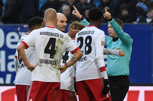 Soccer Football - Bundesliga - Hamburger SV vs Hertha BSC - Volksparkstadion, Hamburg, Germany - March 17, 2018 Hamburg players surround referee Robert Kampka REUTERS/Fabian Bimmer DFL RULES TO LIMIT THE ONLINE USAGE DURING MATCH TIME TO 15 PICTURES PER GAME. IMAGE SEQUENCES TO SIMULATE VIDEO IS NOT ALLOWED AT ANY TIME. FOR FURTHER QUERIES PLEASE CONTACT DFL DIRECTLY AT + 49 69 650050