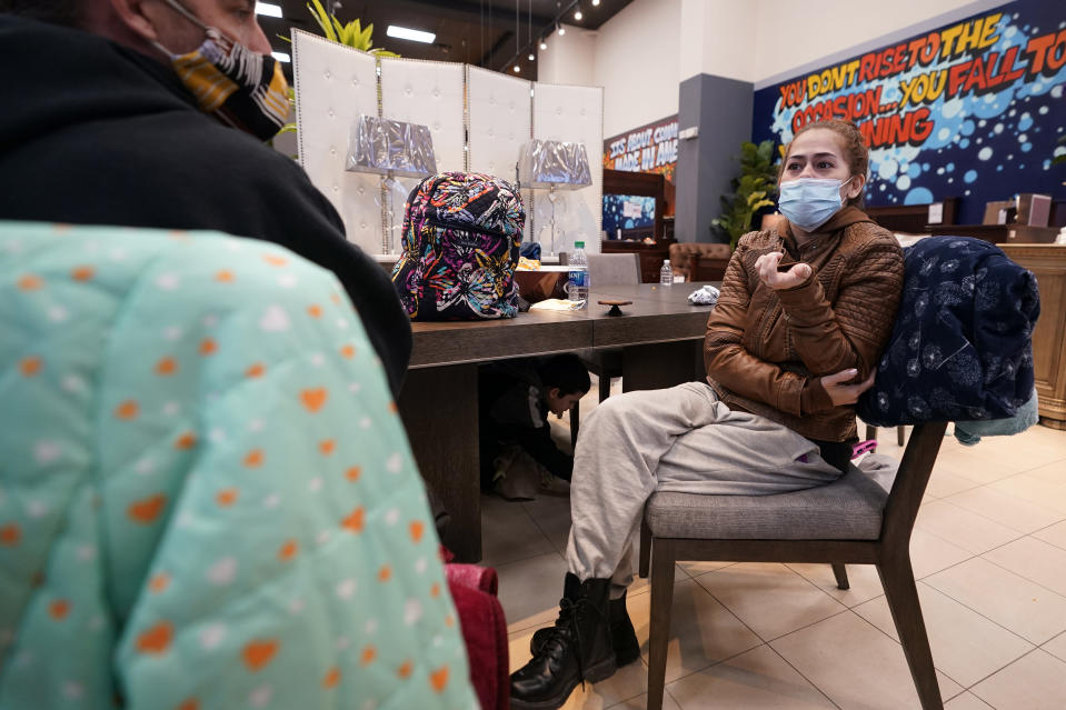 Tina Rios, right, and her husband, Eric Bennis, talk about losing power at their home while sitting inside a Gallery Furniture store which opened as a shelter Wednesday, Feb. 17, 2021, in Houston. Millions in Texas still had no power after a historic snowfall and single-digit temperatures created a surge of demand for electricity to warm up homes unaccustomed to such extreme lows, buckling the state's power grid and causing widespread blackouts. (AP Photo/David J. Phillip)