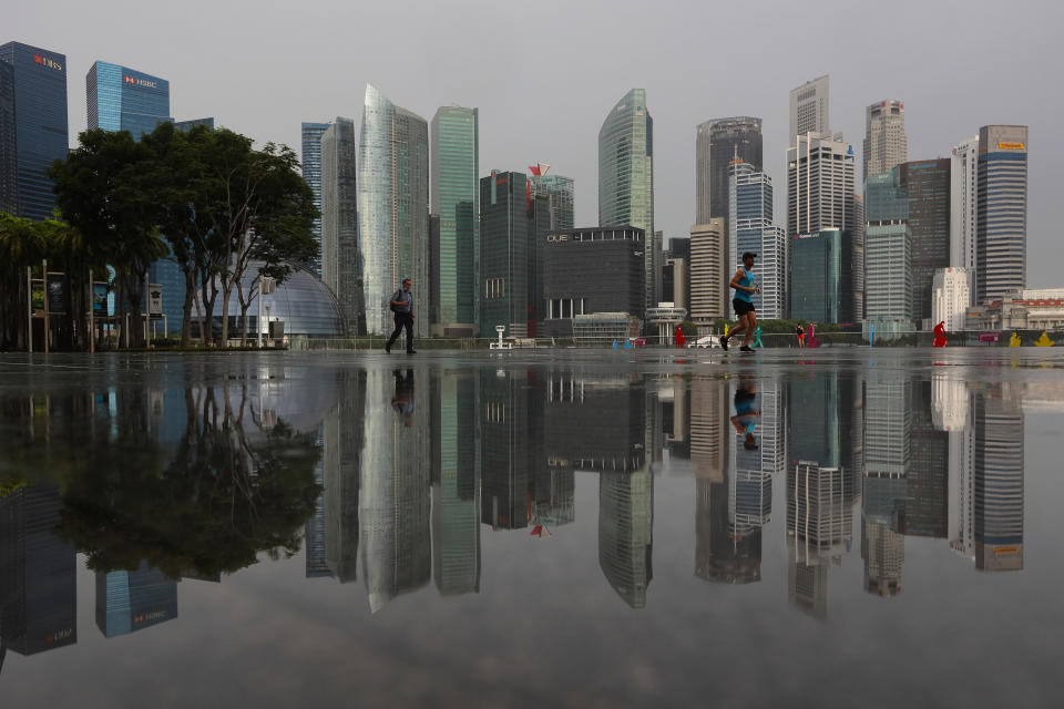 People walk along the Marina Bay waterfront with the central business district seen in the background on July 5, 2021 in Singapore.  (Photo by Suhaimi Abdullah/NurPhoto via Getty Images)