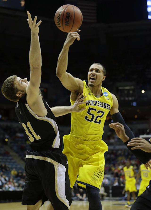 Michigan forward Jordan Morgan (52) and Wofford forward C.J. Neumann (31) battle for a rebound during the first half of a second round NCAA college basketball tournament game Thursday, March 20, 2014, in Milwaukee. (AP Photo/Morry Gash)