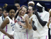 FILE - Connecticut guard Nika Muhl (10), second from right, hugs guard Paige Bueckers (5) after defeating South Carolina in overtime of an NCAA college basketball game in Storrs, Conn., in this Monday, Feb. 8, 2021, file photo. Paige Bueckers is in a class all by herself. UConn's star guard became the first freshman ever to win The Associated Press women's basketball player of the year award Wednesday, March 31, 2021. At left is UConn's Christyn Williams (13). (David Butler/Pool Photo via AP, File)
