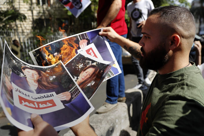 """A supporter of the Shiite Hezbollah and Amal groups burns posters that show the U.S. Ambassador to Lebanon Dorothy Shea, and Arabic that reads: """"Judge Bitar is red line,"""" during a protest against Judge Tarek Bitar who is investigating last year's deadly seaport blast, in front of the Justice Palace, in Beirut, Lebanon, Thursday, Oct. 14, 2021. Lebanon's interior minister said atb least five people have been killed in armed clashes in Beirut that erupted Thursday during protests against the lead investigator into last year's massive blast at the city's port. (AP Photo/Hussein Malla)"""