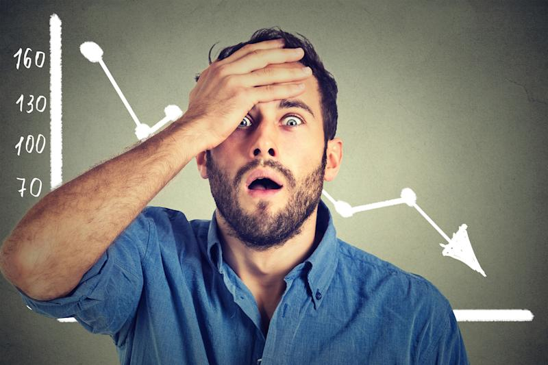 A man holds his hand up to his forehead in front of a chart displaying a declining share price.