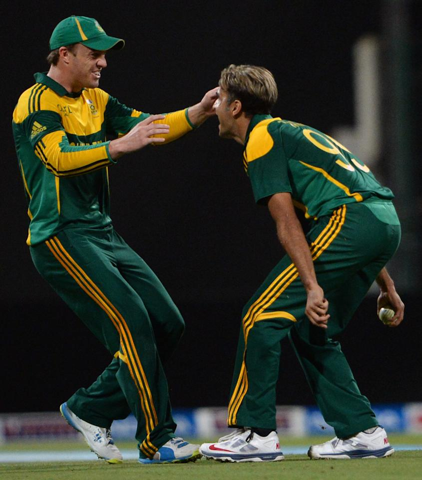 South African bowler Imran Tahir (R) celebrate with his captain AB de Villiers (L) after taking a wicket of Pakistani cricketer Umar Akaml (unseen) during the third day-night international in Sheikh Zayed Cricket Stadium in Abu Dhabi on Novemver 6, 2013. Pakistan were chasing 260 runs target after South Africa made 259 runs for eight wicket in their 50 overs. The five-match series is tied at 1-1. AFP PHOTO/ Asif HASSAN        (Photo credit should read ASIF HASSAN/AFP/Getty Images)