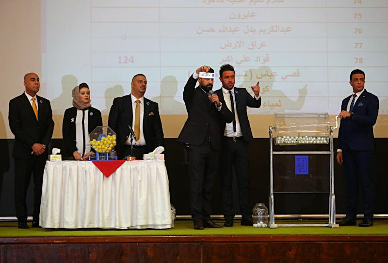 In this Tuesday, Feb. 20, 2018, photo, Iraqi election commission officials hold a lottery of the numbers of lists of electoral coalitions in Baghdad. Iraq's Shiites, Sunnis and Kurds have grown more fragmented and divided ahead of the national elections scheduled for May due to deep differences among each group that have spawned more and smaller alliances seeking to have a bigger share in the new parliament. (AP Photo/Karim Kadim)