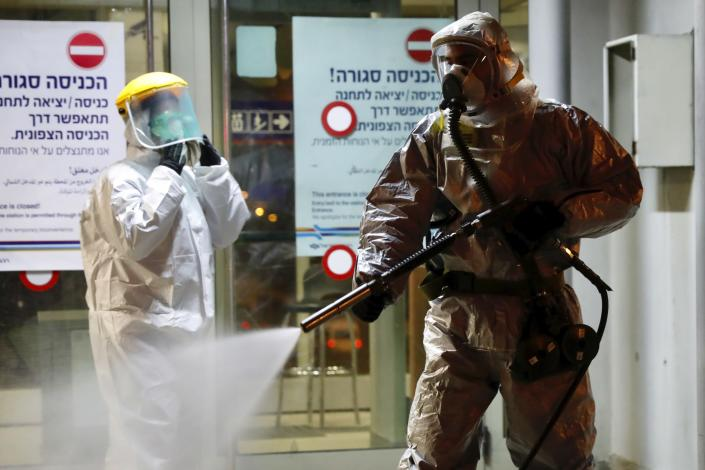‏A firefighter sprays disinfectant as a precaution‏ against the coronavirus at the Moshe Dayan Railway Station in Rishon LeTsiyon, Israel, Sunday, March 22, 2020. (AP Photo/Ariel Schalit)
