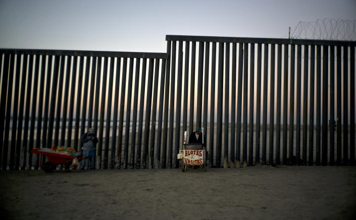 Street vendors stand at the U.S.-Mexico border structure in Tijuana, Mexico, Friday, Nov. 23, 2018. The mayor of Tijuana has declared a humanitarian crisis in his border city and says that he has asked the United Nations for aid to deal with the approximately 5,000 Central American migrants who have arrived in the city. (AP Photo/Ramon Espinosa)