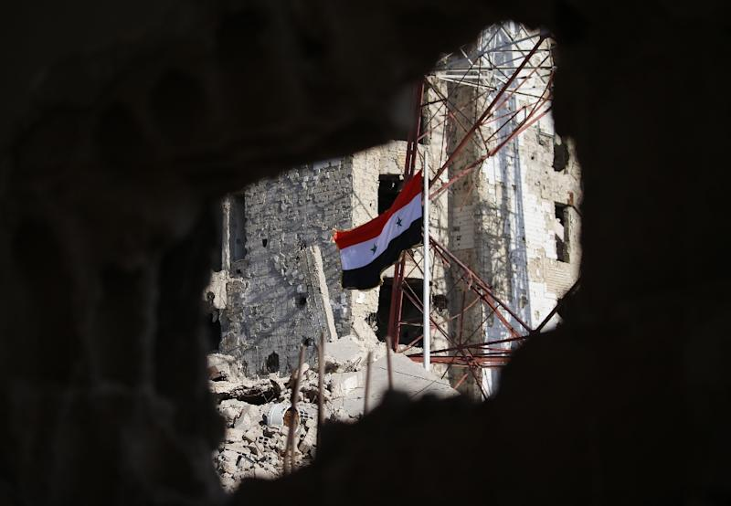 The Syrian national flag flies among damaged buildings in an opposition-held part of the southern city of Daraa on July 12, 2018 (AFP Photo/Mohamad ABAZEED)