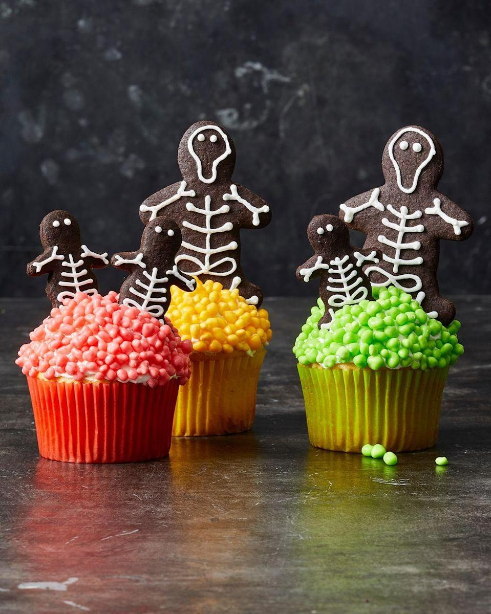 """<p>Neon candy-covered cupcakes are the perfect resting place for this skeleton cookie family. </p><p><em><a href=""""https://www.goodhousekeeping.com/food-recipes/party-ideas/a28592955/chocolate-skeleton-cookie-cupcakes-recipe/"""" rel=""""nofollow noopener"""" target=""""_blank"""" data-ylk=""""slk:Get the recipe for Chocolate Skeleton Cookie Cupcakes »"""" class=""""link rapid-noclick-resp"""">Get the recipe for Chocolate Skeleton Cookie Cupcakes »</a></em></p>"""