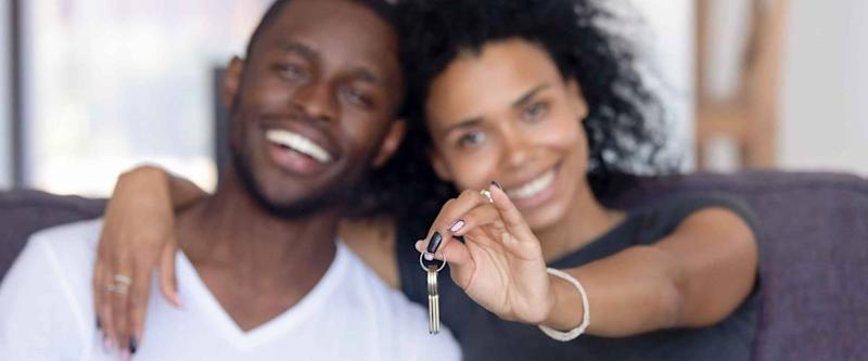 Excited young Black couple show keys to new home.