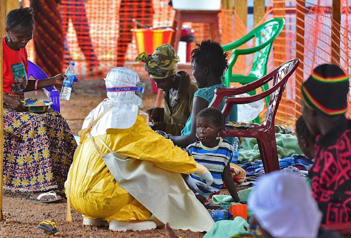 An MSF medical worker feeds an Ebola child victim at an MSF facility in Kailahun, Sierra Leone on August 15, 2014 (AFP Photo/Carl De Souza )