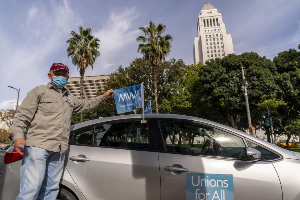 Uber driver Jose Luis Guevara, a member of the Mobile Workers Alliance, pauses for a picture outside Los Angeles City Hall Tuesday, Jan. 12, 2021. Drivers for app-based ride-hailing and delivery services are suing to overturn a California ballot initiative that makes them independent contractors instead of employees eligible for benefits and job protections. The lawsuit filed Tuesday, Jan. 12, 2021 in the California Supreme Court said Proposition 22 is unconstitutional because it limits the power of the Legislature to grant workers the right to organize and excludes drivers from being eligible for workers' compensation. (AP Photo/Damian Dovarganes)