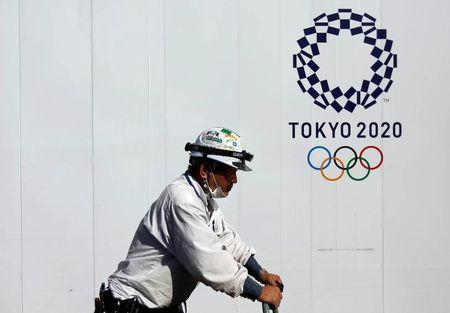 A construction worker walks past at a construction site of a building displaying Tokyo 2020 Olympics emblem in Tokyo, Japan May 23, 2017. REUTERS/Issei Kato