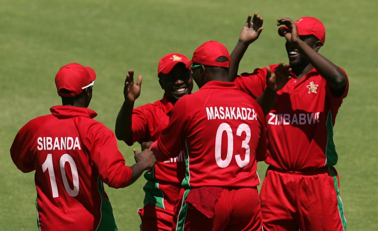 Zimbabwe players celebrate a wicket during the first game of the three match ODI cricket series between Pakistan and hosts Zimbabwe at the Harare Sports Club on August 27, 2013.AFP PHOTO / JEKESAI NJIKIZANA        (Photo credit should read JEKESAI NJIKIZANA/AFP/Getty Images)