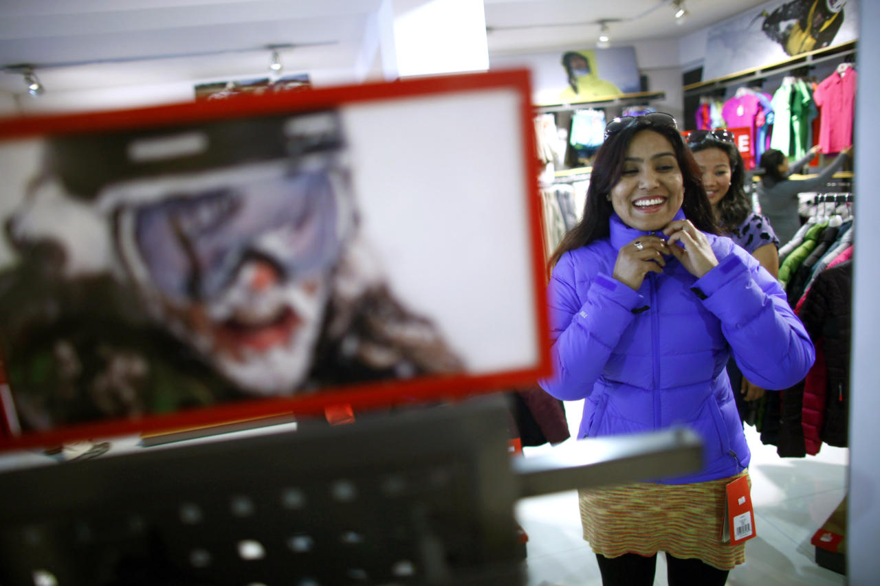 In this Tuesday, Feb. 21, 2013 photo, Nepalese climber Pujan Acharya tries on climbing gear at a store in Katmandu, Nepal. Aiming to change the all-male image of mountaineering in the country, a group of Nepalese women have embarked on a mission to climb the tallest mountain on each of the seven continents. The women, aged between 21 and 32, have already climbed Everest in Asia, Kosciuszko in Australia and Elbrus in Europe and are preparing next week to climb Mount Kilimanjaro in Africa to mark International Women's Day. (AP Photo/Niranjan Shrestha)