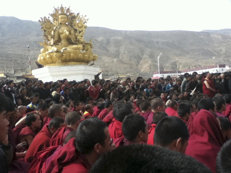 FILE - In this Wednesday, March 14, 2012 photo released on Thursday, March 15, 2012 by Freetibet.org, Tibetan monks gather in protest after the latest self-immolation attempt in Tongren, a monastery town in Qinghai province, western China. China has released a documentary accusing the Dalai Lama of orchestrating a wave of self-immolations by Tibetans, in its most elaborate attempt so far to shape international opinion about the protests against Chinese rule. (AP Photo/Freetibet.org)