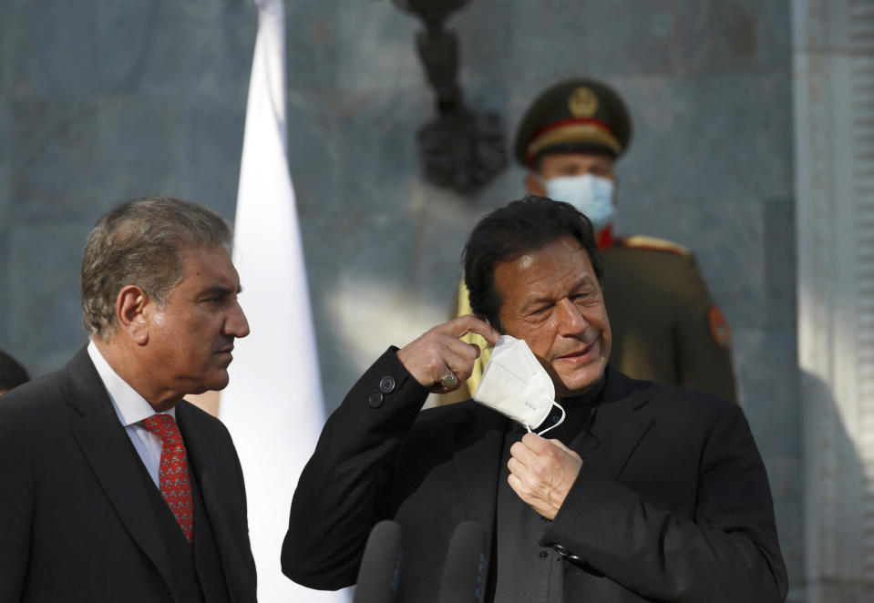 Pakistan Prime Minister Imran Khan removes his face mask during a joint news conference with Afghan President Ashraf Ghani at the Presidential Palace in Kabul, Afghanistan, Thursday, Nov. 19, 2020. (AP Photo/Rahmat Gul)