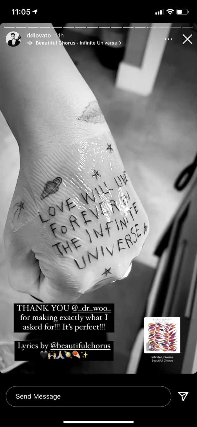 """<p>Demi showed off their latest tat, which features song lyrics written across the top of their left hand, on their Instagram Stories. """"THANK YOU @_dr_woo_ for making exactly what I asked for!!!"""" they wrote. """"It's perfect."""" </p><p>The tattoo reads, """"Love will live forever in the infinite universe,"""" lyrics from the song """"Infinite Universe"""" by Beautiful Chorus. The singer surrounded the lyric with stars and a planet. </p>"""