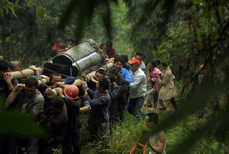 Villagers carry a coffin on April 22, 2013, after a magnitude 7.0 earthquake hit Lushan, Sichuan Province