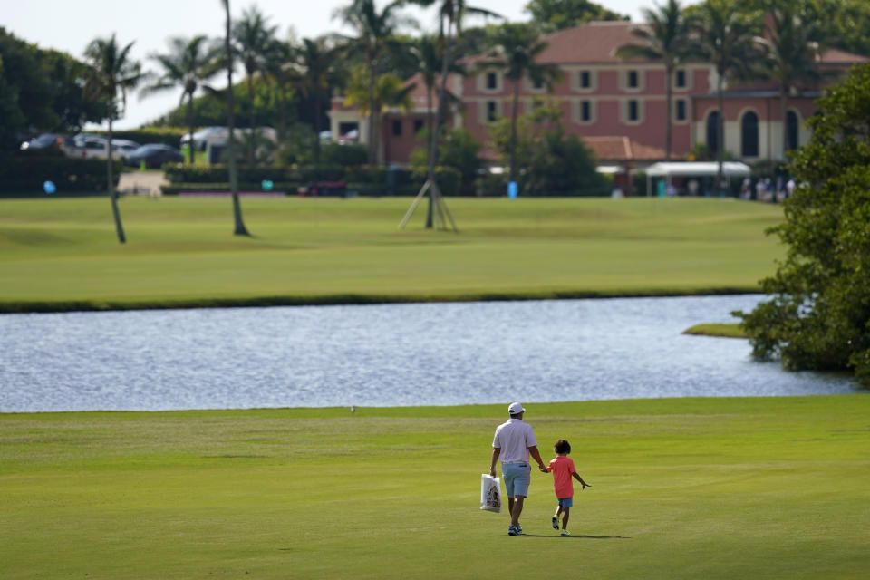 A man and child walk along the course during a practice day for the Walker Cup golf tournament at Seminole Golf Club in Juno Beach, Fla., Friday, May 7, 2021. (AP Photo/Gerald Herbert)