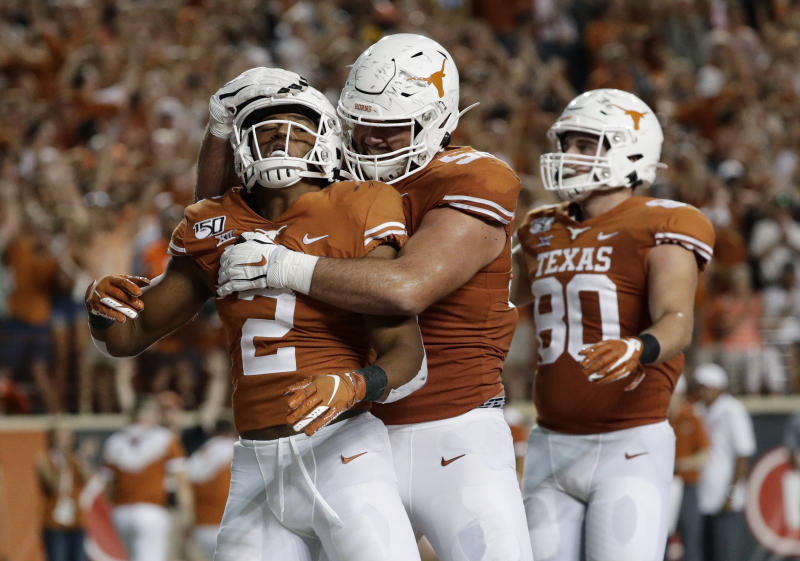 Texas' Roschon Johnson (2) celebrates his touchdown run with teammates during the second half of an NCAA college football game against Oklahoma State, Saturday, Sept. 21, 2019, in Austin, Texas. (AP Photo/Eric Gay)