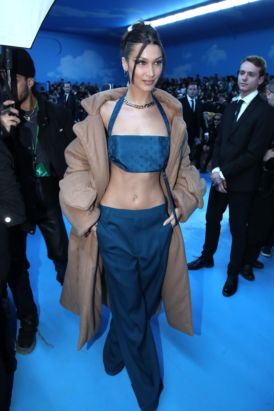 """<p>Bella brought back the '00s with this low-rise crop-top <a href=""""https://www.popsugar.com/fashion/bella-hadid-louis-vuitton-menswear-paris-fashion-week-2020-47114615"""" class=""""link rapid-noclick-resp"""" rel=""""nofollow noopener"""" target=""""_blank"""" data-ylk=""""slk:combo by Louis Vuitton"""">combo by Louis Vuitton</a>.</p>"""