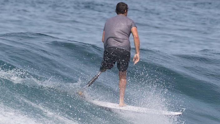 Chris Blowes surfing with his prosthetic leg