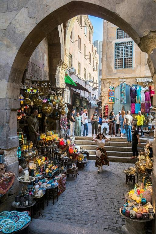 Tourists walk past shops selling copper and stained-glass lamps at the Khan el-Khalili bazaar area in Egypt's capital Cairo