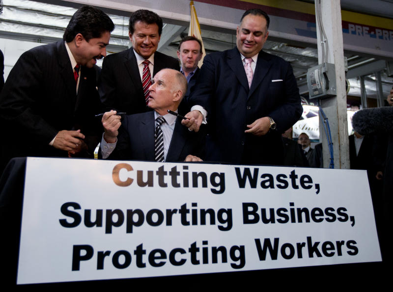 California Gov. Jerry Brown, seated,  borrows a pen from California Assembly member Jose Solorio, left, as he signs a bill aimed at worker's compensation costs at a printing company in San Diego. Looking on from right are California Assembly Speaker John Perez, Art Polaski of the California Labor Federation, and California Assembly member Marty Block.   Brown signed the bill intended to reduce workers' compensation costs for California businesses while increasing benefits to injured workers. (AP Photo/Gregory Bull)