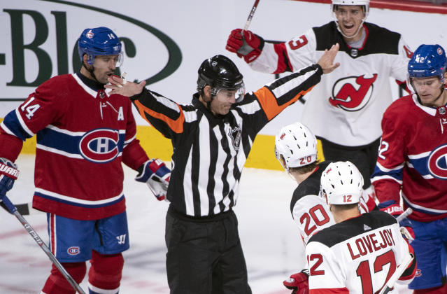 In this photo taken Sept. 17, 2018, referee Wes McCauley, center, gestures as the Montreal Canadiens face the New Jersey Devils during third-period preseason NHL hockey game action in Montreal. An informal poll of NHL players leaves no doubt as to who the most popular referee is: Veteran McCauley. (Paul Chiasson/The Canadian Press via AP)