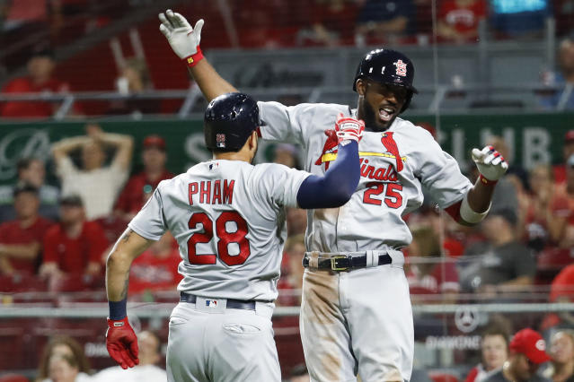 St. Louis Cardinals' Dexter Fowler (25) celebrates with Tommy Pham (28) after hitting a two-run home run off Cincinnati Reds relief pitcher Amir Garrett during the 11th inning of a baseball game Tuesday, July 24, 2018, in Cincinnati. The Cardinals won 4-2. (AP Photo/John Minchillo)