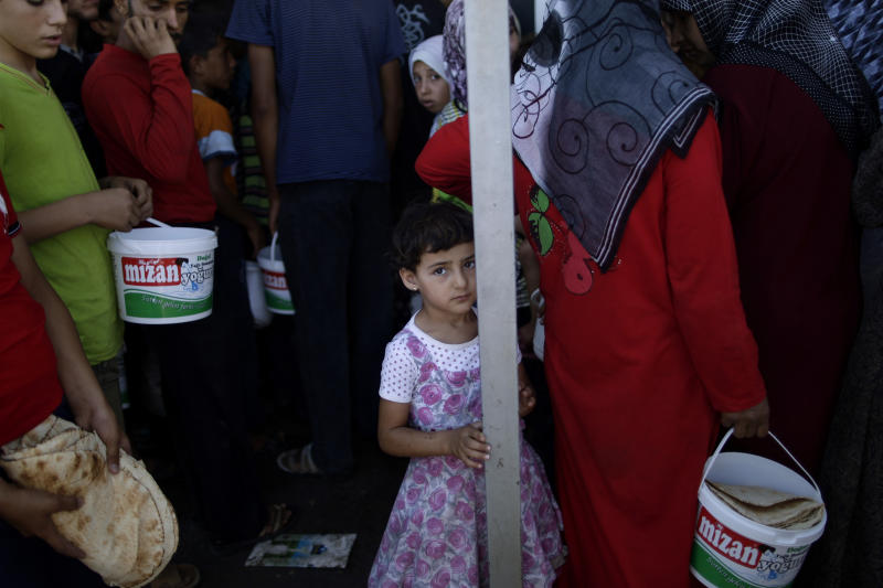 A Syrian girl, bottom center, who fled her home, due to fighting between the Syrian army and the rebels, waits her turn to buy bread and eggs from a store, as she and others take refuge at the Bab Al-Salameh border crossing, in hopes of entering one of the refugee camps in Turkey, near the Syrian town of Azaz, Monday, Sept. 3, 2012. (AP Photo/Muhammed Muheisen)